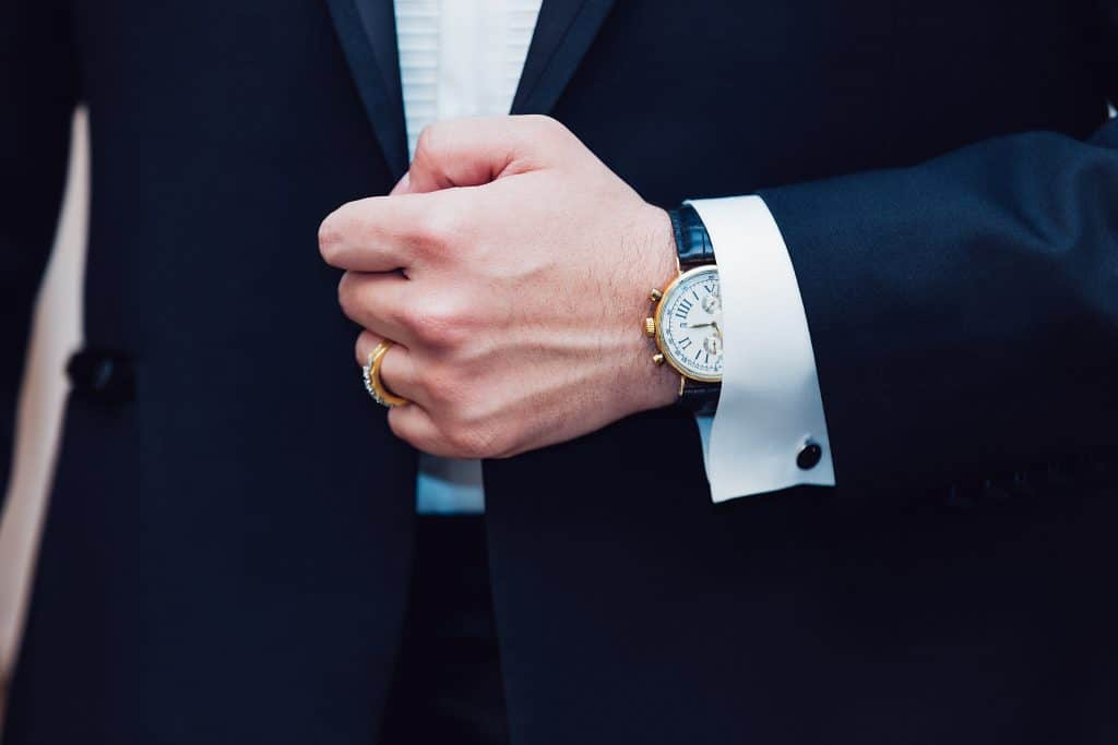 suit from a garment bag and a watch